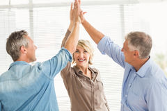 Smiling business colleagues giving high-five. Three smiling business colleagues giving high-five at the office Royalty Free Stock Photo