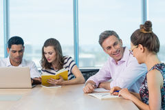 Smiling business colleagues interacting with each other and using laptop Royalty Free Stock Images