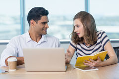 Smiling business colleagues interacting with each other while using laptop Royalty Free Stock Images