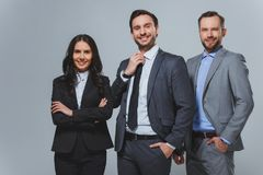 Smiling business colleagues looking at camera. On grey stock photos