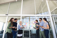 Smiling business colleagues standing against glass wall Royalty Free Stock Photos