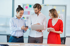 Smiling business colleagues using mobile phone, digital tablet and laptop Royalty Free Stock Photo