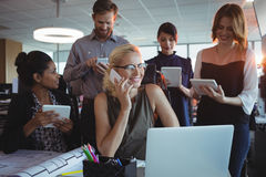 Smiling business colleagues using mobile phones and digital tablets together Royalty Free Stock Image