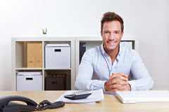 Smiling business consultant. In office at desk Royalty Free Stock Photo