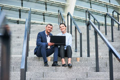 Smiling business couple with laptop. stock photography