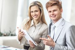 Smiling business couple looking at digital tablet screen.  royalty free stock image