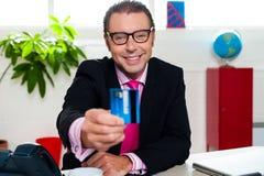Smiling business executive displaying credit card Royalty Free Stock Photos