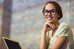 Smiling business executive with hand on chin in office Royalty Free Stock Photo