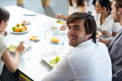 Smiling business executive having meal in office stock image