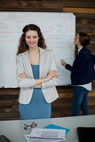 Smiling business executive standing with arms crossed while colleague working in background Royalty Free Stock Images
