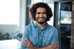 Smiling business executive standing with arms crossed in office Stock Photo