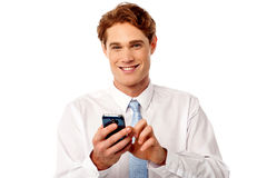 Smiling business executive using mobile phone. Handsome young executive texting with smartphone Stock Photos