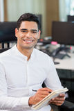 Smiling business executive writing on notebook in office Royalty Free Stock Photo