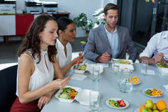 Smiling business executives having meal in office Stock Photography