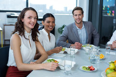 Smiling business executives having meal in office royalty free stock photo