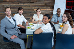 Smiling business executives having meal in office stock photos