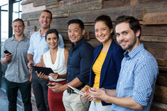 Smiling business executives using mobile phone and digital tablet in office Stock Photos