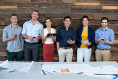 Smiling business executives using mobile phone and digital tablet in office. Portrait of smiling business executives using mobile phone and digital tablet in Royalty Free Stock Photo