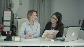 Smiling business female team working with tablet pc in the office stock video footage