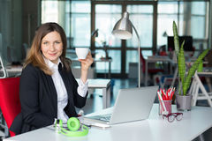 Smiling Business Lady in official clothing holding Coffee Mug Royalty Free Stock Photos