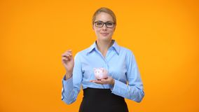 Smiling business lady putting coin piggybank bright background, bank deposit