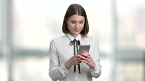 Smiling business lady using her smartphone. Beautiful short hair business woman with smartphone on blurred background stock footage