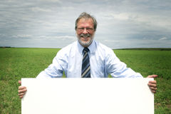 Smiling business man. Senior business man holding a blank board in a meadow Stock Photography