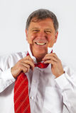 Smiling business man binding his red tie Royalty Free Stock Photography