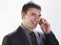 Smiling business man with cellphone. Full length of a happy businessman displaying a laptop on white background royalty free stock images
