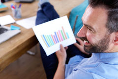 Smiling business man with charts at his desk Royalty Free Stock Photos