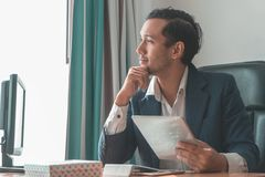 Smiling business man happily looking out the windows stock image