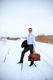 Smiling business man holding bag in winter field Royalty Free Stock Photography