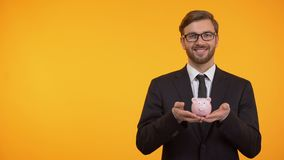 Smiling business man holding piggy-bank, saving money concept, orange background