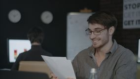 Smiling business man looking document paper on workplace in dark office. Joyful financial analyst satisfied successful report. Happy businessman working in stock footage
