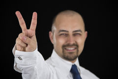 Smiling business man making peace sign with his fingers Royalty Free Stock Image