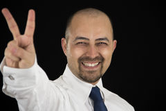Smiling business man making peace sign with his fingers Stock Photos