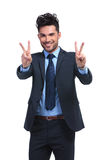 Smiling business man making the victory hand gesture Royalty Free Stock Photos