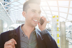 Smiling business man on mobile phone call with bag. Close up portrait of smiling traveling business man on mobile phone call with bag Royalty Free Stock Photo