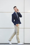 Smiling business man on mobile phone call walking. Full body portrait of smiling business man on mobile phone call walking Royalty Free Stock Photo