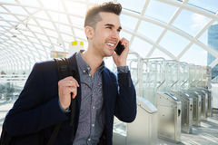 Smiling business man on phone walking by turnstile Stock Photo