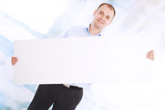 Smiling business man presents a white banner Royalty Free Stock Photos