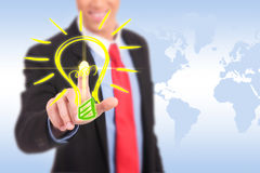 Smiling business man pushing a light bulb button Stock Images