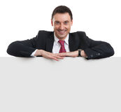 Smiling business man showing blank signboard Stock Images
