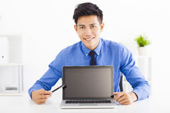 smiling business man showing laptop in the office Royalty Free Stock Image