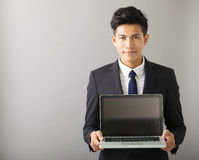 Smiling business man showing laptop. Young smiling business man showing laptop royalty free stock image