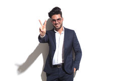 Smiling business man showing the victory sign. Smiling business man wearing sunglasses showing the victory sign while leaning on a white wall with one hand in Royalty Free Stock Photography