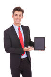 Smiling business man showing you his tablet pad Royalty Free Stock Images