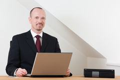 Smiling business man sitting at desk with laptop. Business man sitting at wooden desk, grey laptop in front of him smiling at the viewer. Scandinavian simple Stock Photo