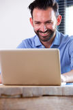 Smiling business man sitting at his desk and using laptop Royalty Free Stock Photos