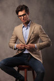 Smiling business man sitting and unbuttoning his coat Stock Photography